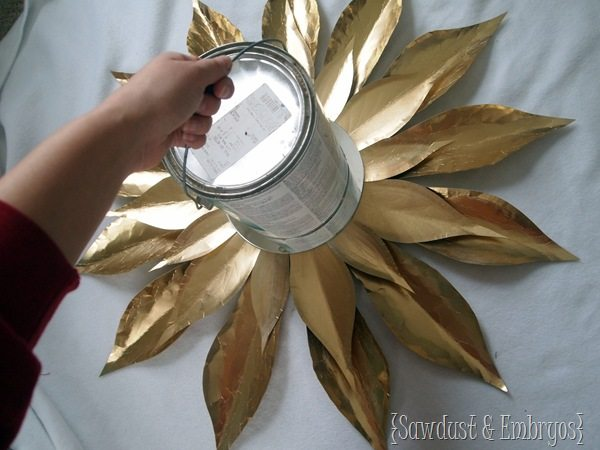 Put something heavy on your DIY Starburst Mirror while the glue is drying {Sawdust and Embryos}