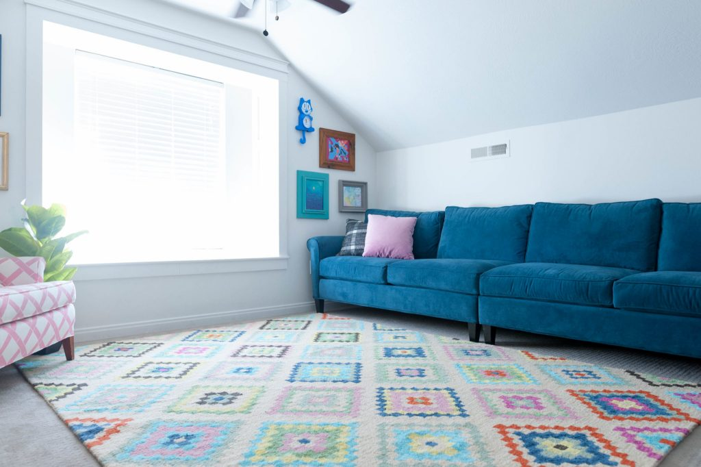 Pink and Navy with multi colored accents in kids play room with navy blue couch